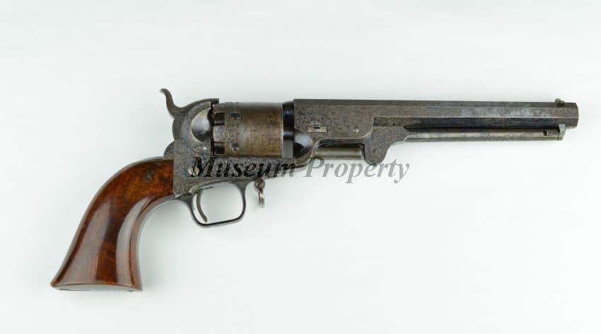 Revolver Colt modèle Navy 1851, calibre .36, 6 coups, poignée en noyer monobloc, cadre en acier trempé, finition bleuie avec montage argenté sur la sangle arrière et le pontet. Ce revolver appartenait à Jefferson Davis et fut saisit lors de sa capture en le 4 mai 1865 en Géorgie par la Cavalerie du Michigan.